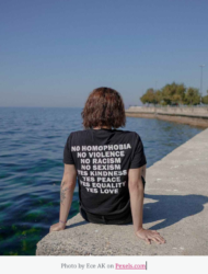 Person sitting by water with message t-shirt