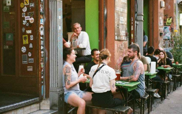 Sidewalk cafe a group gathered around is talking
