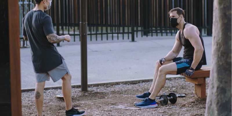 two guys in a park with workout equipment and face masks