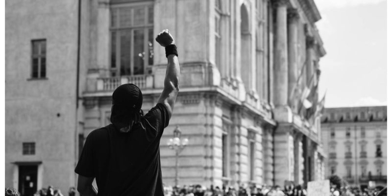 Person with a raised fist at a rally