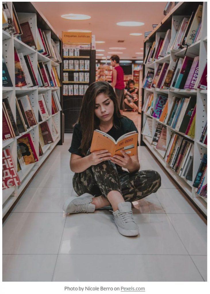 girl reading in library courtesy Nicole Berro on Pexels.com