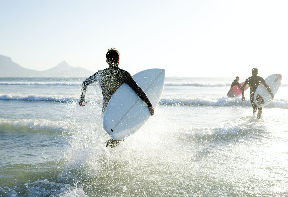 Surfers running out to the waves